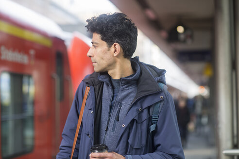 Man with backpack and coffee to go on platform - SGF02166