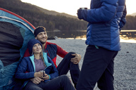 Smiling young couple with friend sitting at tent at lakeshore - PNEF00430