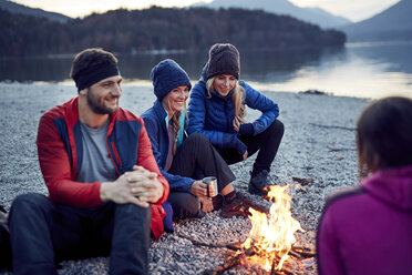 Smiling friends sitting around campfire at lakeshore - PNEF00433