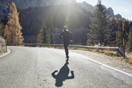 Man running on mountain road - PNEF00436