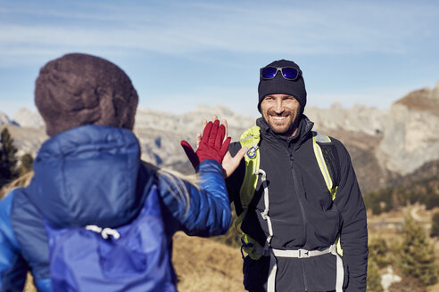 Smiling man and woman hiking in the mountains high fiving - PNEF00448