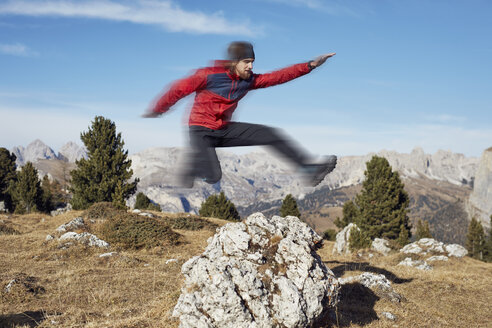 Young man jumping over rock in mountains - PNEF00451