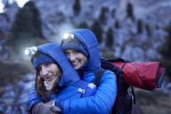 Two happy young women wearing headlamps embracing in the mountains - PNEF00457