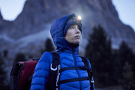Young woman wearing headlamp at dusk in the mountains - PNEF00460