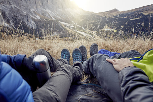 Legs of couple sitting in tent in the mountains - PNEF00469