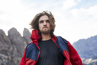 Portait of young man with windswept hair in the mountains - PNEF00478