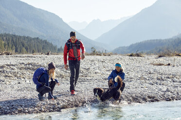 Germany, Bavaria, Karwendel, group of friends hiking with dog at the riverside - PNEF00487