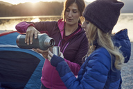 Two women with hot drink camping at lakeshore - PNEF00505