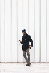 Italy, Milan, African american man with smartphone and headphone - MAUF01277