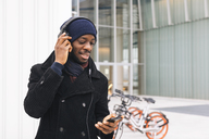 Italy, Milan, African american man with smartphone and headphone - MAUF01280