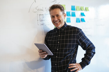 Smiling businessman with tablet in office leaning against whiteboard - EBSF02085