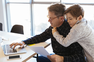 Businessman using laptop at desk in office with son embracing him - EBSF02097