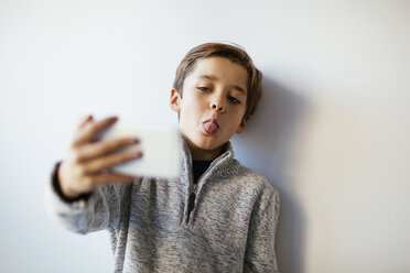 Boy taking selfie sticking out tongue - EBSF02109