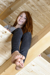Portrait of laughing redheaded teenage girl sitting in attic - LBF01758