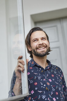Portrait of laughing man at open window - PNEF00510
