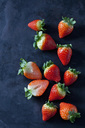 Sliced and whole strawberries on dark ground - CSF28887