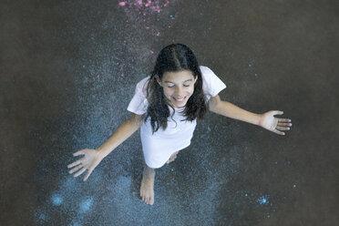 Happy girl enjoying shower of colour powder - PSTF00093