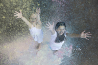 Portrait of two friends throwing colour powder in the air - PSTF00096