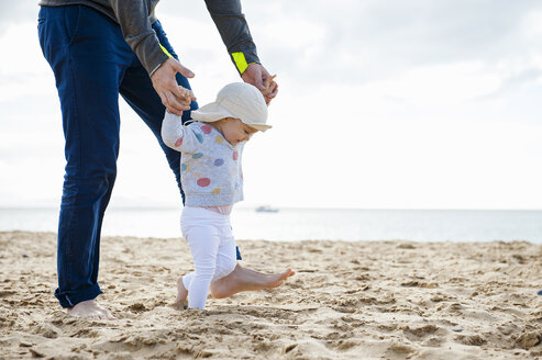 Spain, Lanzarote, baby girl walking on the beach with the help of his father - DIGF03229