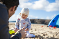 Spain, Lanzarote, happy baby girl  playing with father on the beach - DIGF03232