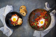 Shakshouka with chick peas in pan and slices of roasted baguette - LVF06668