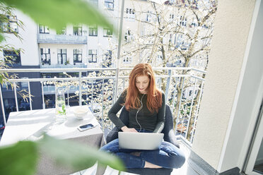 Redheaded woman sitting on balcony using laptop and earphones in spring - FMKF04765