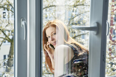 Portrait of redheaded woman on the phone leaning out of window in spring - FMKF04768