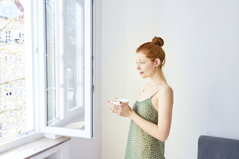 Portrait of pensive woman with bowl of white coffee standing near open window - FMKF04771
