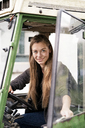 Portrait of smiling woman driving a tractor - PESF00940