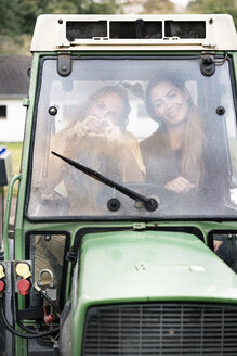 Two woman sitting in tractor, forming heart with hands - PESF00943