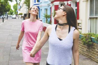 Two happy teenage girls walking hand in hand in the city - WPEF00015