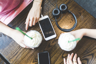 Two women at table with milkshakes, cell phones and headphone - WPEF00027