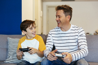 Happy father and son playing video game on couch at home - EBSF02112