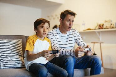 Father and son playing video game on couch at home - EBSF02115