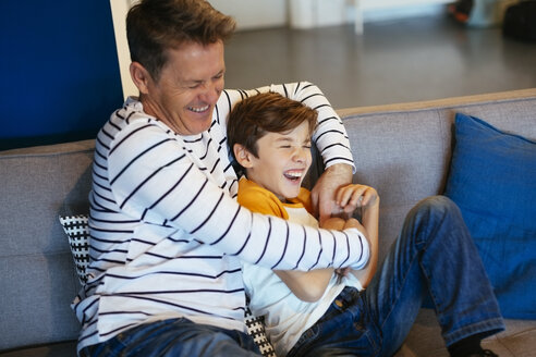 Carefree father and son having fun on couch at home - EBSF02124