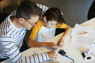 Father and son assembling a construction kit with wind turbine model - EBSF02130
