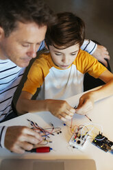 Father and son assembling an electronic construction kit - EBSF02136
