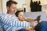 Father and son with earbuds and tablet on couch at home - EBSF02142