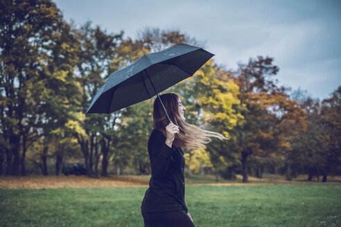 Happy young woman with umbrella walking in autumnal park - JSCF00029