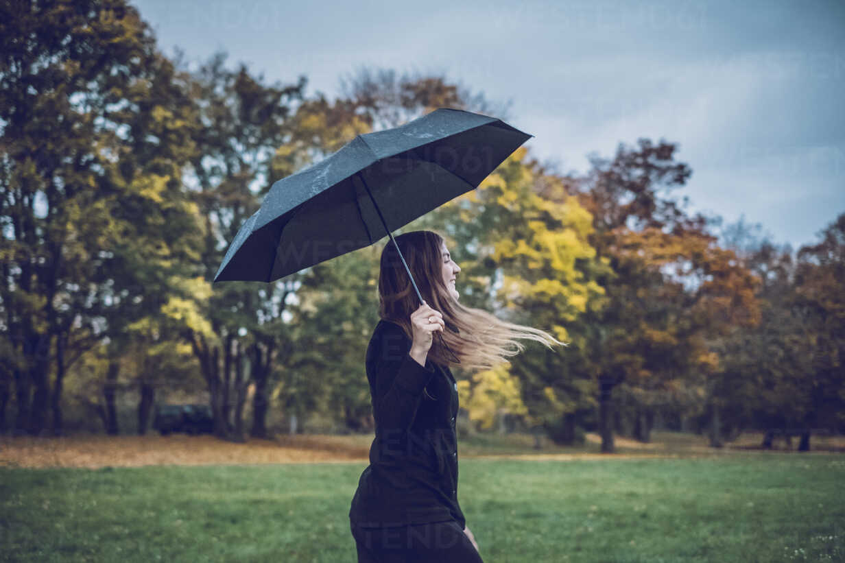 Happy young woman with umbrella walking in autumnal park - JSCF00029 - Jonathan Schöps/Westend61