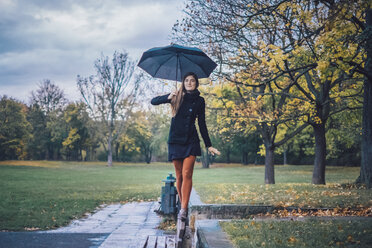Young woman with umbrella balancing on backrest of bench in autumnal park - JSCF00032