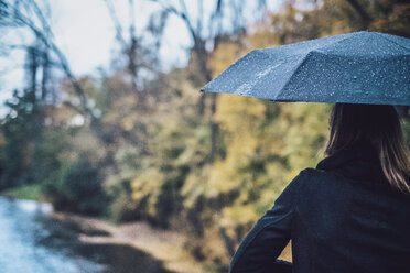 Back view of young woman with wet umbrella in autumn - JSCF00035