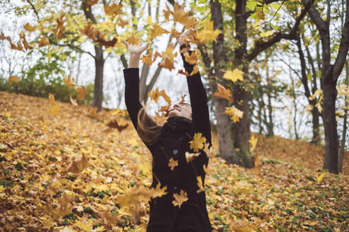 Happy young woman throwing autumn leaves into the air - JSCF00038