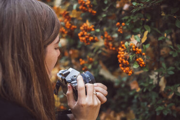 Young woman taking photos with old camera in autumnal nature - JSCF00041