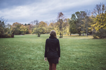 Back view of young woman walking on a meadow in autumnal park - JSCF00047