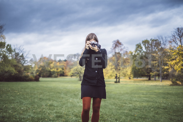 Young woman taking pictures with camera on a meadow in autumnal park - JSCF00050 - Jonathan Schöps/Westend61