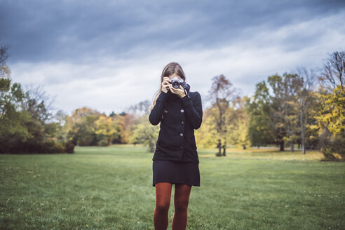 Young woman taking pictures with camera on a meadow in autumnal park - JSCF00050