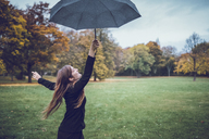 Happy young woman dancing with umbrella in autumnal park - JSCF00053