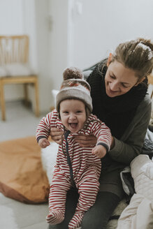 Mother holding happy baby wearing sleepers and wooly hat at home - DWF00328