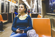 USA, New York, woman with cell phone in subway - WPEF00048